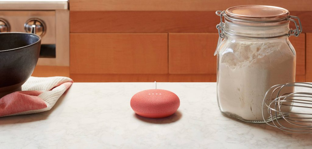 A Google Home Mini placed in a kitchen counter