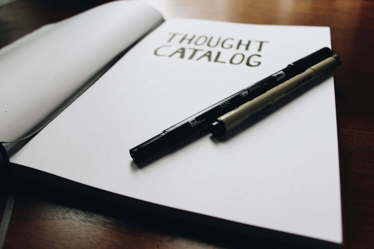 "A notepad with the text ""Thought Catalog"" and two pens on top of it"