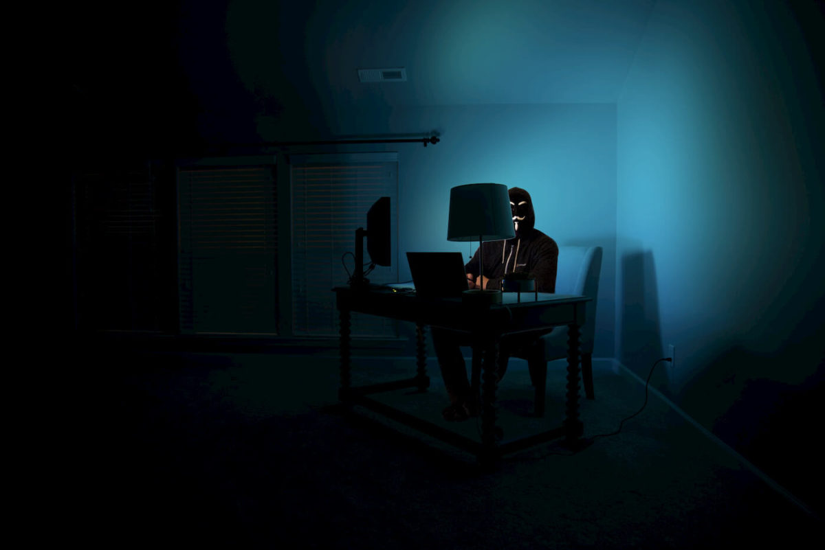 Man sitting on a desk in a dark coerner with a laptop