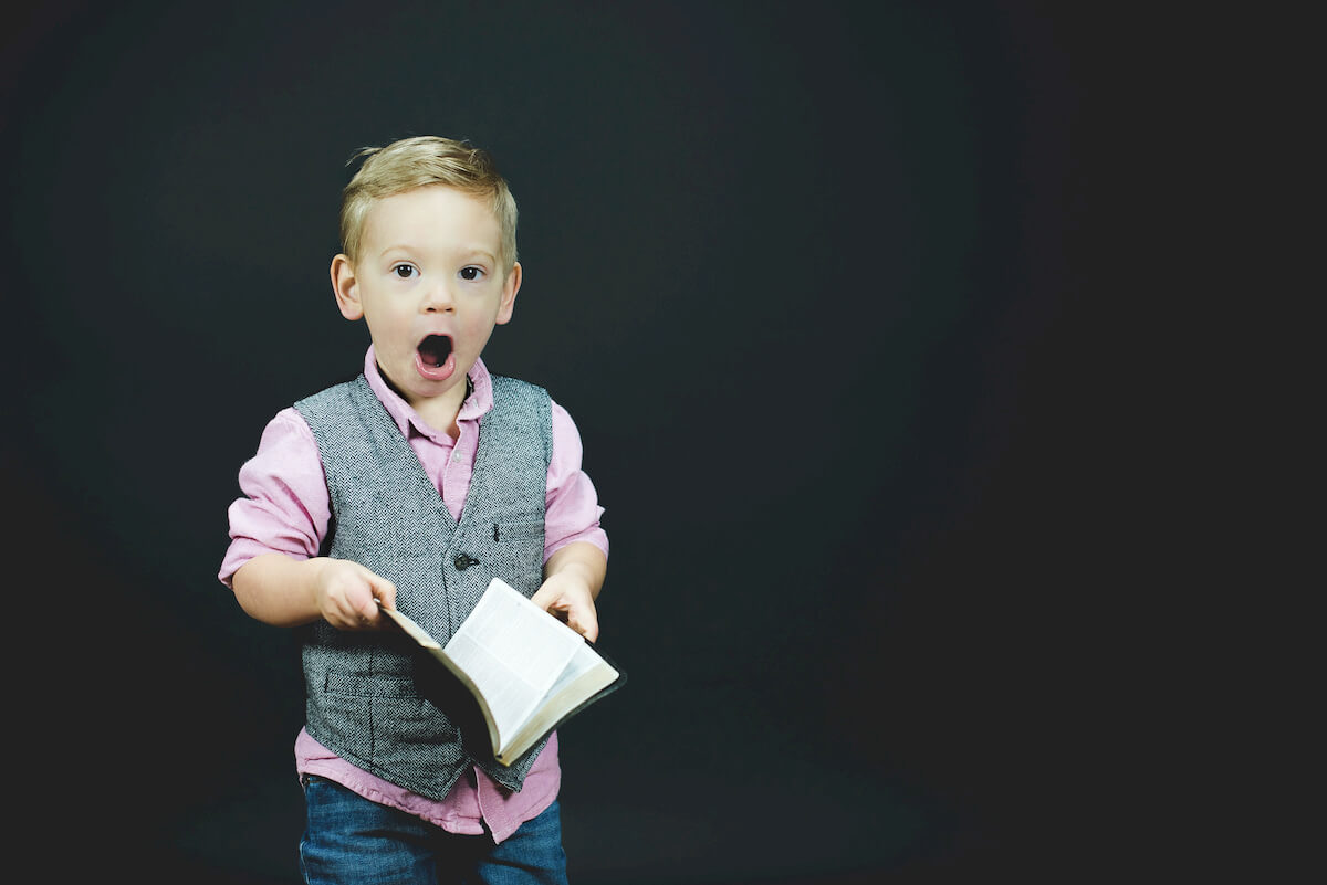 Kid with open mouth holding a book