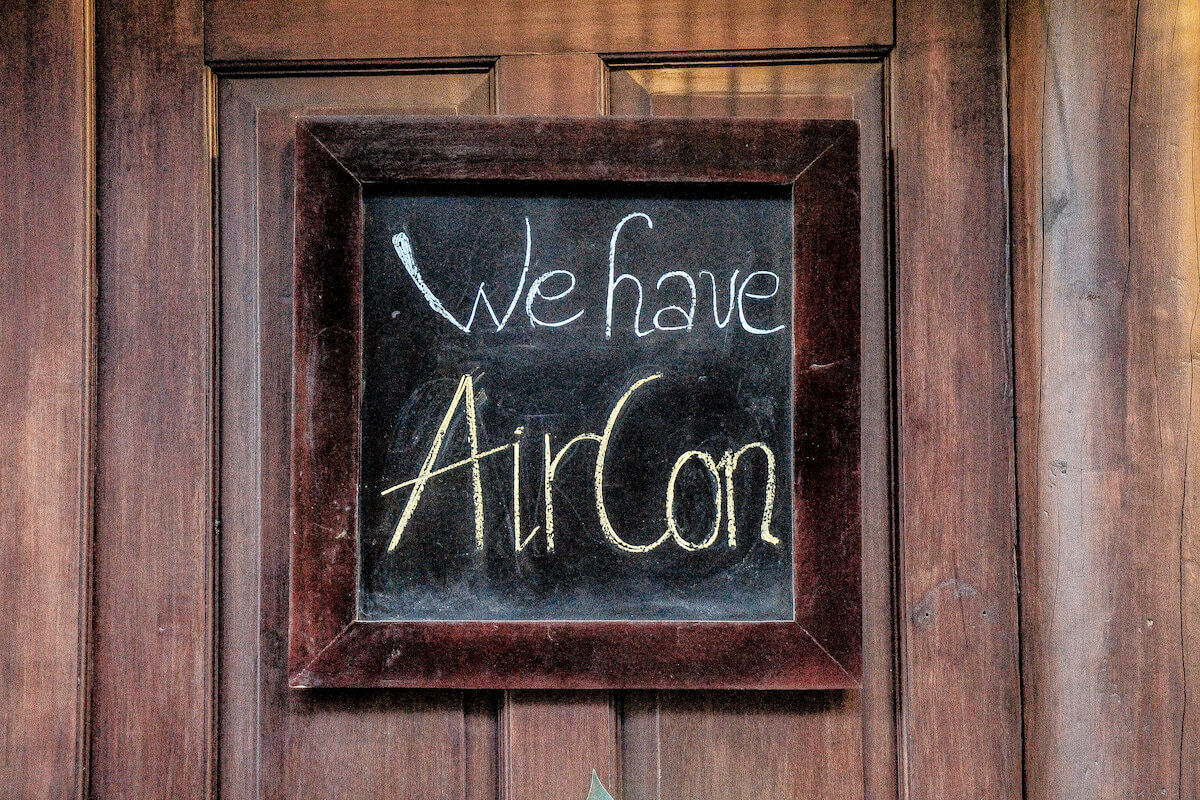 A sign on a wooden door that says We Have Aircon