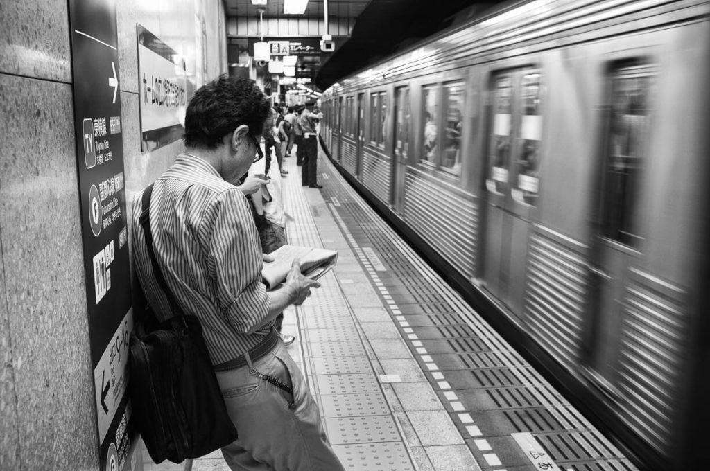 A man reads the newspaper in the Tokyo metro platform